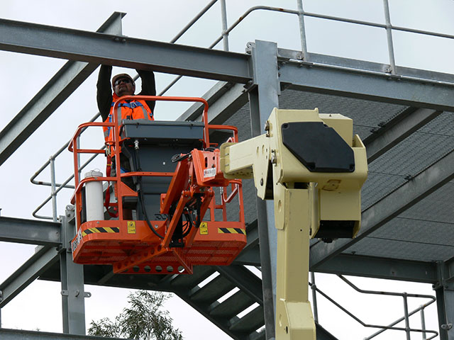 Worker on a elevating work platform with overhead structures that may pose a crush risk