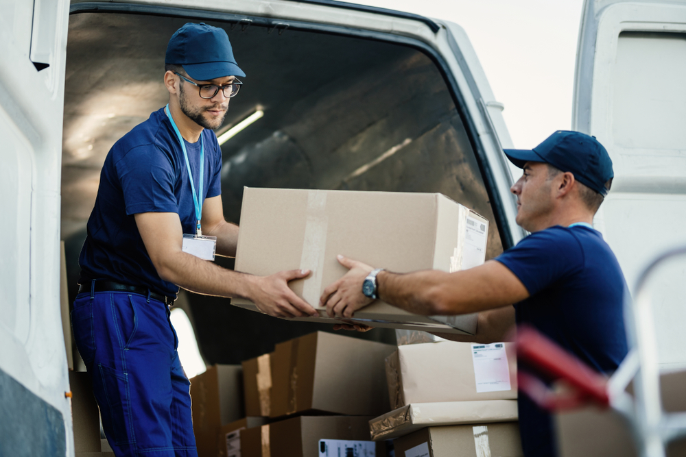 Two delivery drivers unloading parcels
