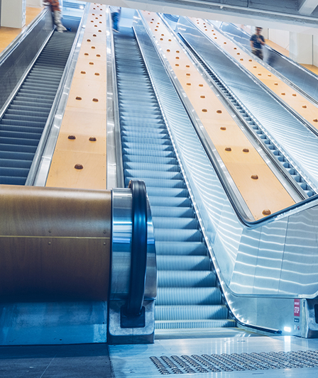 Escalators in a railway station with yellow void in-fills
