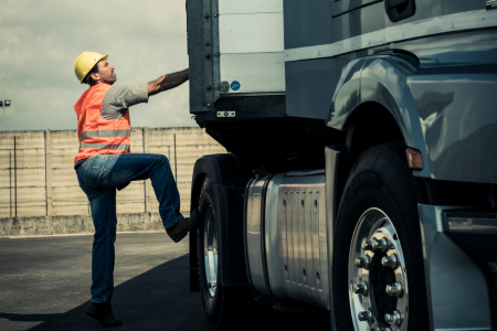 Truck driver climbing into truck