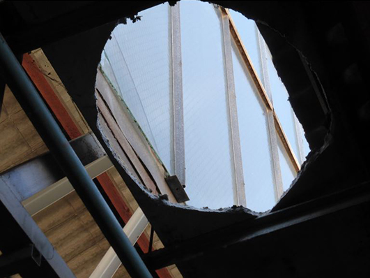 Close up of the hole in a metal roof where a worker fell through