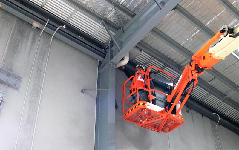 Worker on an elevating work platform near a roof