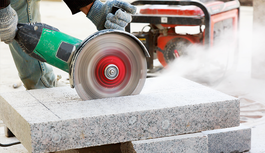 Image of stone benchtop being cut by grinder.